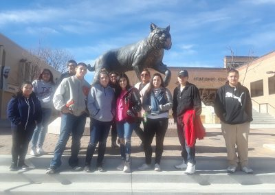 Michael poses with his classmates infront of the wildcat statue at Johnson & Wales.