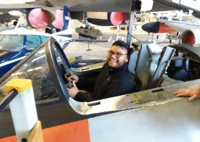 Eric in an airplane cockpit at the Wings Over the Rockies Musuem