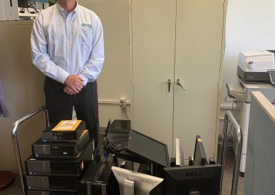 Russ stands infront of a cart full of computer towers and monitors. He has his hands folded infront of him and is smiling.