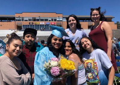 Ashley poses with her family at her high school graduation. There are 7 people in the picture including Ashley and she is wearing her light blue graduation cap and gown.