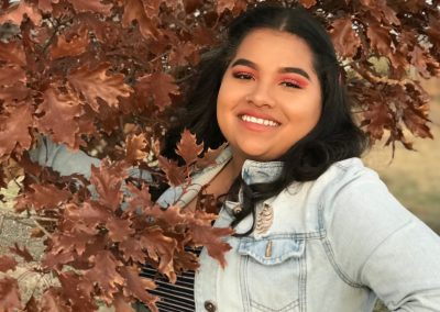 Ashley stands smiling beside a tree with leaves turning red for the fall. She is smiling.