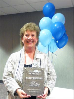 Holly stands holding a glass plaque for her Principal of the Year award. There are blue balloons behind her.