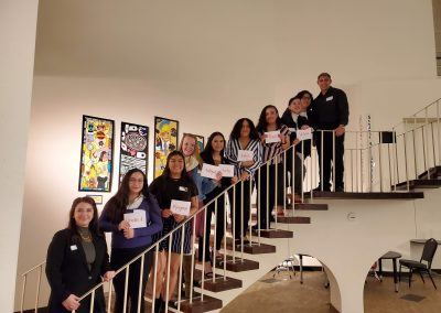 Maryann stands on a staircase with her fellow scholarship recipients form her school. They are smiling and holding up white cards with their names written in cursive, orange font.