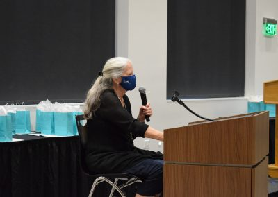 Terri sits at a podium holding a microphone during our 2021 Awards Ceremony. She is wearing a mask.