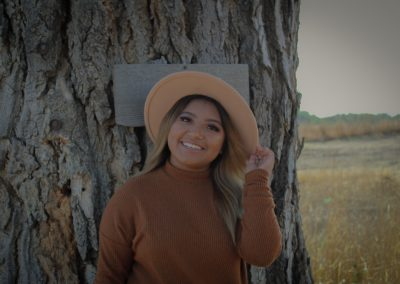 Evelin stands smiling infront of a tree. She is wearing a straw sunhat that she is holding with her left hand.