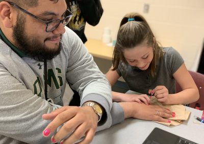 A Dream Team student paints Eric's nails bright pink.