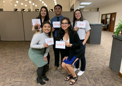 Evelin poses with the other four scholarship recipients from her school. They are all holding envelopes with their names written in curly, orange font.