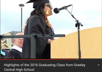 Yessica stands at a podium as she speaks at her high school graduation.