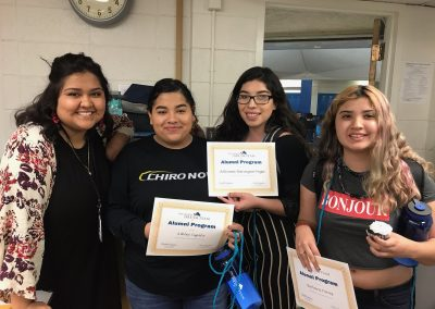 Ashley poses with three others at her senior celebration. They are holding certificates and smiling.