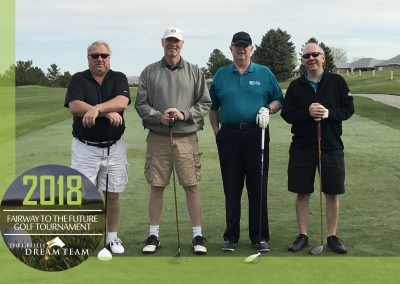 Russ stands holding a golf club and smiling as he poses with his teammates at our 2018 Golf Tournament