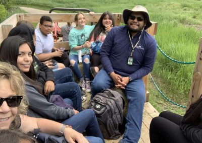 Eric smiles as he sits with students on a hay ride.
