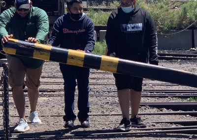 Eric and two students stand behind the lever for the railroad turntable, pushing it to move the train tracks.