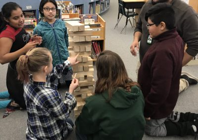 Eric kneels with a group of students around a Jenga tower.
