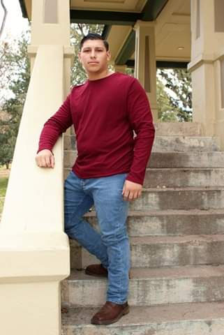 Michael poses on a staircase with his arm resting on the railing.