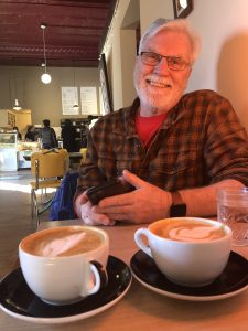 Dr. Reinsvold sits at a table with coffee