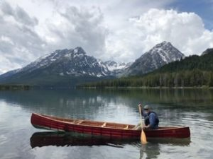Dr. Reinsvold sits and smiles in a canoe in the middle of a lake with mountains in the background