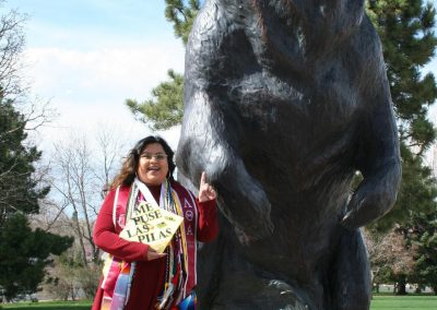 """Yessica poses with a statue of the UNC Bear. She is holding her graduation cap, which reads """"me puse las pilas."""""""