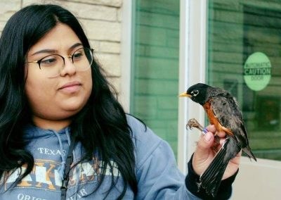 Yessica stands holding the feet of a robin.