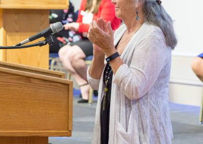 Terri stands behind a podium applauding for the 2019 scholarship recipients.