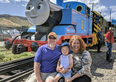 Brandi Lynn sits outside a train sized model of Thomas the Tank Engine with her husband and son, smiling.