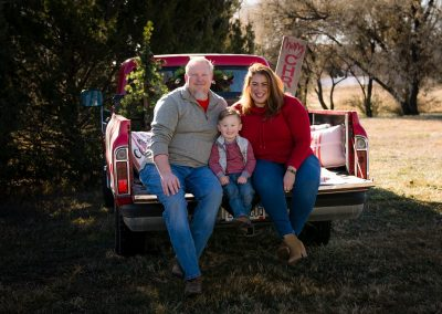 Brandi Lynn poses with her husband and son in the back of a red truck, dressed in Christmas colored sweaters