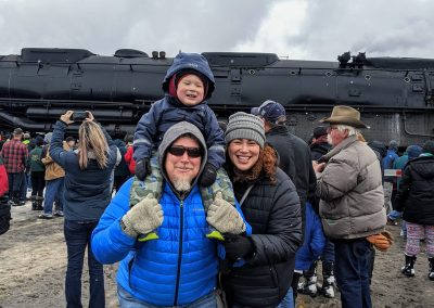 Brandi Lynn poses with her son and husband infront of a train, smiling. Her son is on her husband's shoulders.