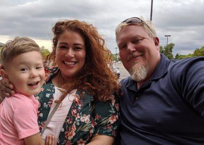 Brandi Lynn, her husband, and son pose, smiling